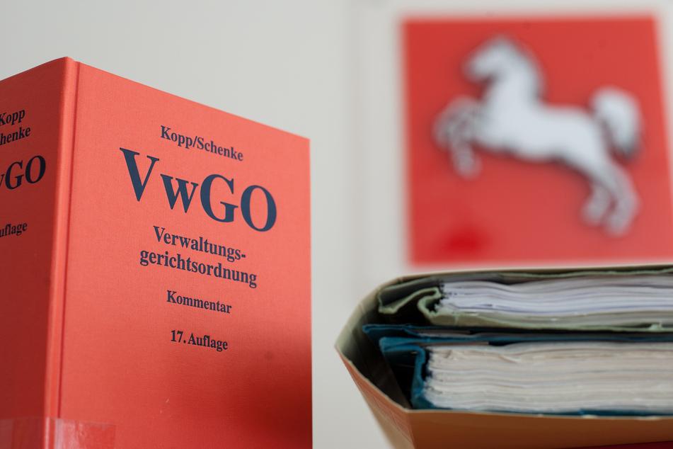 Die Verwaltungsgerichtsordnung steht neben Akten im Niedersächsischen Oberverwaltungsgericht (OVG) auf einem Tisch.