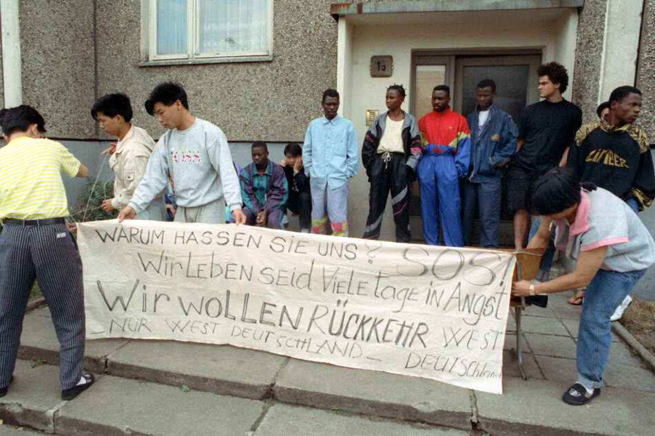 """""""Warum hassen Sie uns"""" steht auf einem Plakat, das Asylbewerber hochhalten. (Archivbild)."""