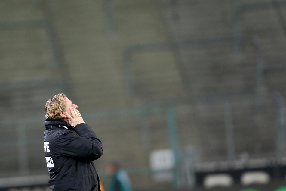 Der Kölner Trainer Markus Gisdol schaut zum Himmel. Das Spiel findet wegen des Coronavirus ohne Zuschauer als Geisterspiel statt.