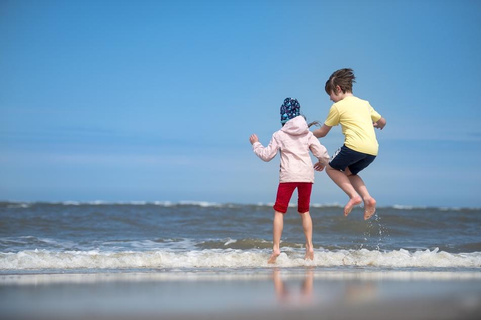 Zwei Kinder spielen am Strand.
