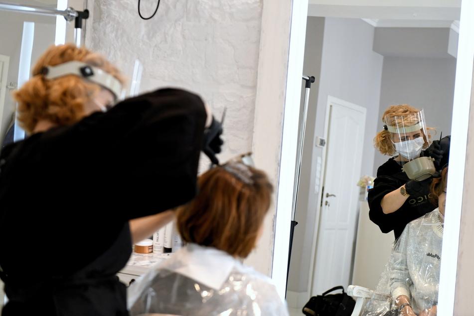 Eine Friseurin schneidet einer Kundin in ihrem Friseursalon in Polen die Haare. Restaurants, Bars, Friseur- und Schönheitssalons durften am 18. Mai unter Einhaltung bestimmter Hygienemaßnahmen wieder öffnen.