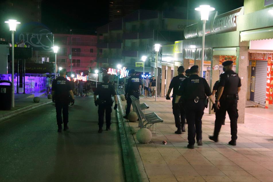 Polizeibeamte mit Mundschutz patrouillieren nachts auf der Straße Punta Ballena im Touristenort Magaluf.
