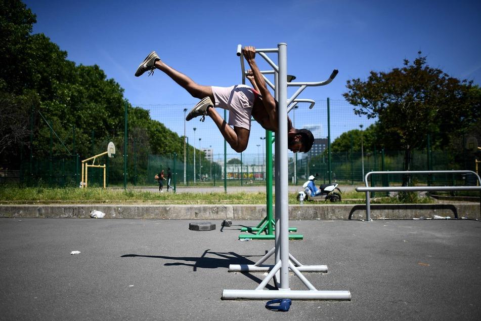 Ein Mann trainiert an einem Sportgerät in einem Park in Paris.