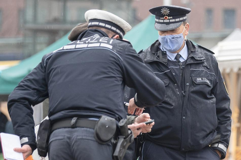 Polizeibeamte kontrollieren während einer Schwerpunktkontrolle zur Einhaltung der Corona-Maßnahmen auf einem Wochenmarkt einen Marktbesucher.
