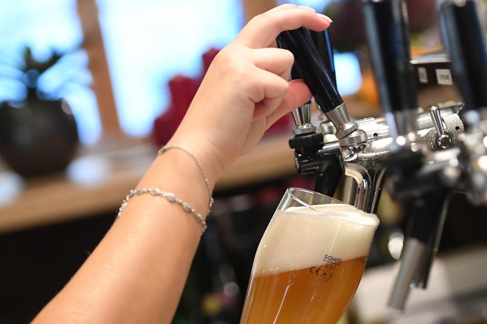 Eine Bedienung zapft Bier in einem Wirtshaus.