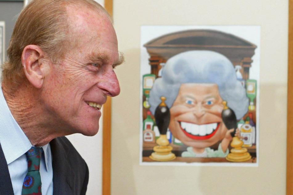 12. April 2002: Prinz Philip lächelt beim Betrachten einer Trogg-Karrikatur zum Thronjubiläum der Queen.