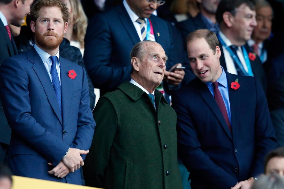 Prinz Harry (l) und sein Bruder Prinz William (r) stehen mit ihrem Großvater Prinz Philip vor Beginn des Rugby World Cup Finales zwischen Neuseeland und Australien im Twickenham Stadion. Werden sich die beiden Brüder wieder versöhnen?