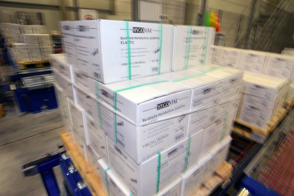 Kartons mit medizinischer Schutzkleidung stehen in einem Lager.