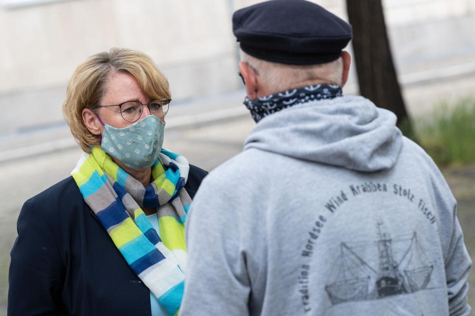 Barbara Otte-Kinast, Niedersachsens Landwirtschaftsministerin (CDU), trägt einen Mundschutz, während sie bei der Mahnwache des Landesfischereiverbandes Weser-Ems vor dem Landtag mit einem Fischer spricht.