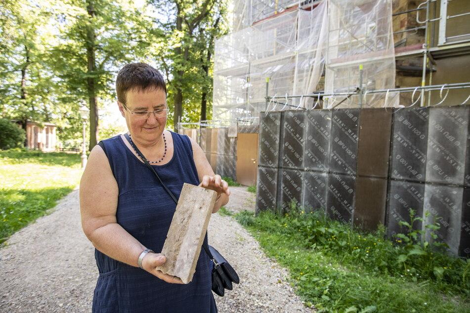 Pfarramtsleiterin Gabriele Führer (59) zeigt einen der Chemnitzer Porphyrtuff-Steine.