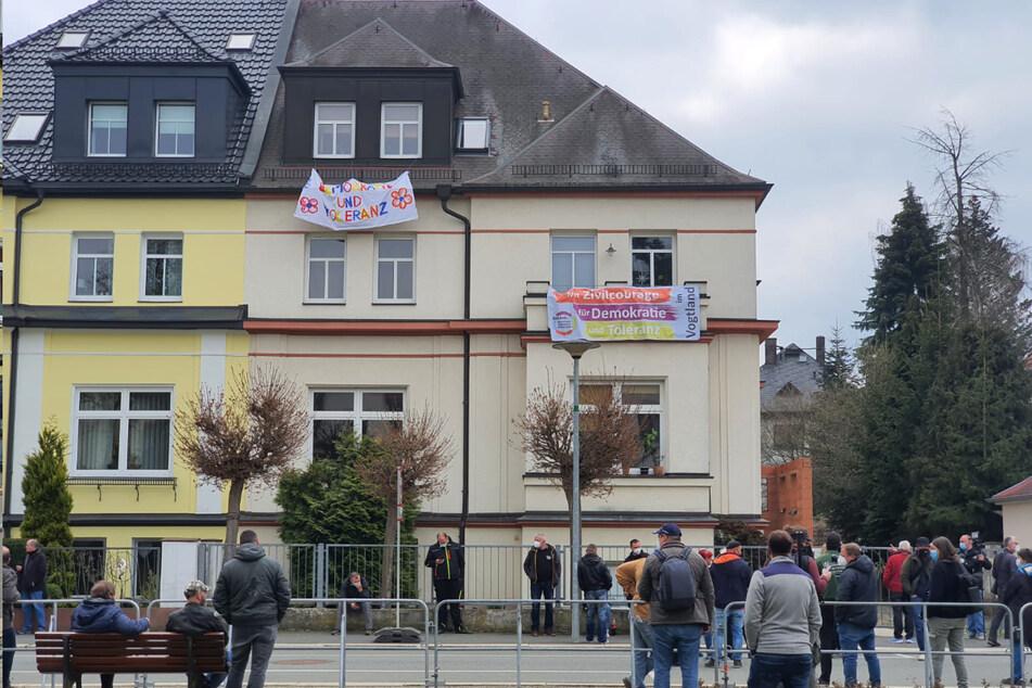 Anwohner protestieren mit Transparenten gegen die Demo.