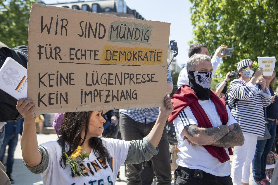 """Gegen die """"Lügenpresse"""" und einen """"Impfzwang"""" richtet sich die Aufschrift auf dem Plakat einer Frau, die sich vor der Alten Oper in Frankfurt an einer Kundgebung gegen die Corona-Maßnahmen der Regierung richtete."""