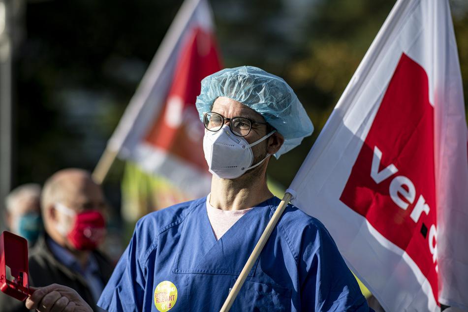 Ein Arzt mit Mund-Nasen-Schutz und OP-Haube steht mit einer Verdi-Flagge vor dem Kongresshotel in Potsdam. (Symbolbild)