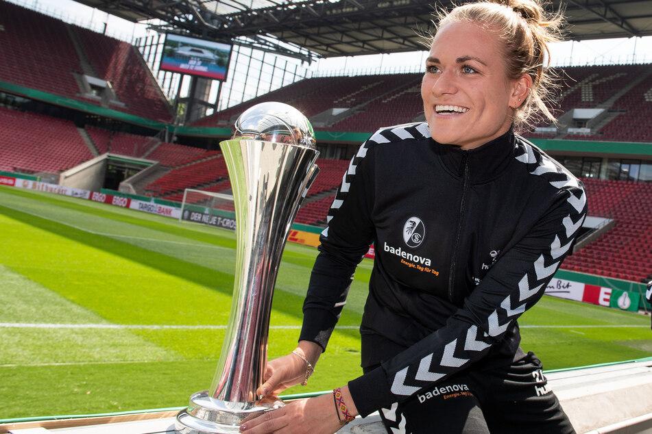 Clara Schöne vom SC Freiburg sitzt im RheinEnergieStadion neben dem DFB-Pokal der Frauen (Archivbild).