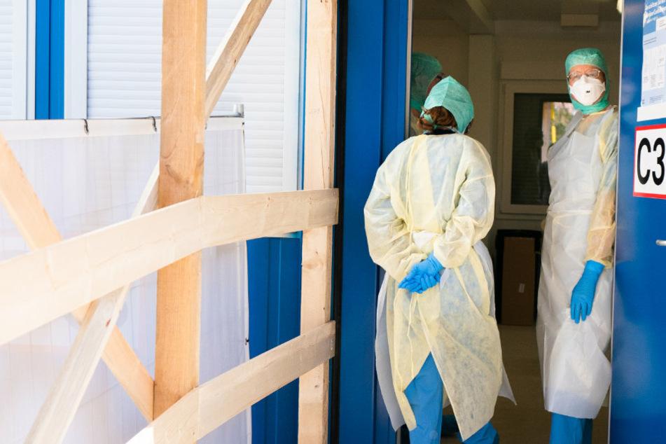 Ärzte betreten ein österreichisches Krankenhaus in Schutzkleidung.