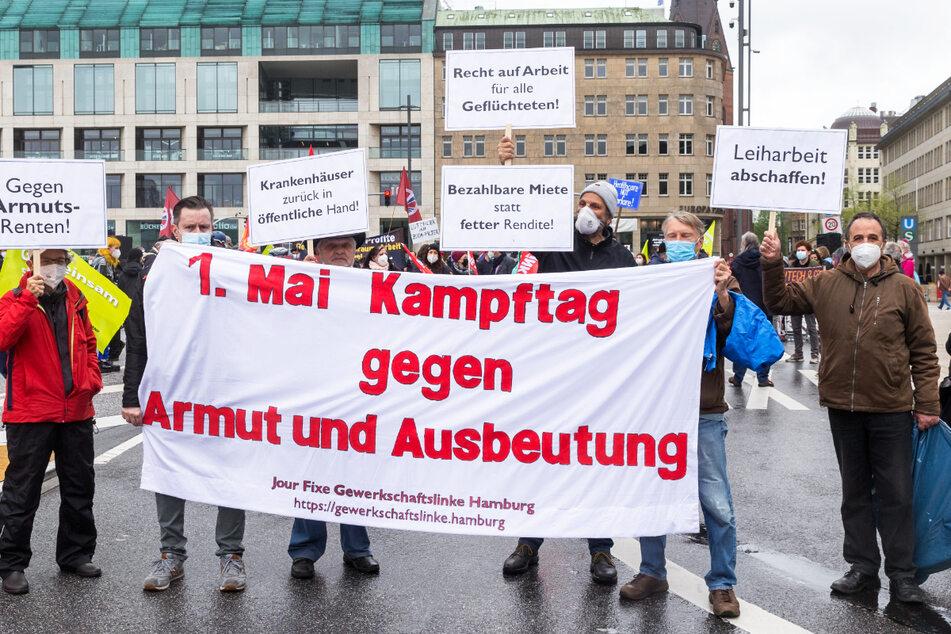 """Teilnehmer halten ein Transparent mit der Aufschrift """"1. Mai Kampftag gegen Armut und Ausbeutung"""" hoch. Linke Gruppen haben heute unter dem Motto """"Sozialer Protest lässt sich nicht verbieten"""" in Hamburg demonstriert."""