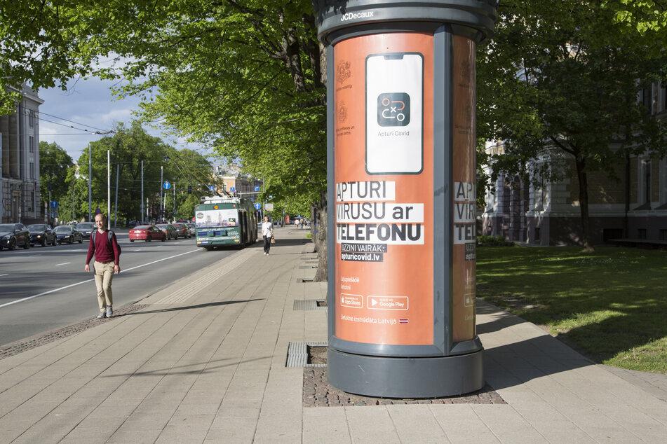 Ein Werbeplakat für die lettische Corona-Warn-App hängt an einer nahezu menschenleeren Straße in einer Litfaßsäule.