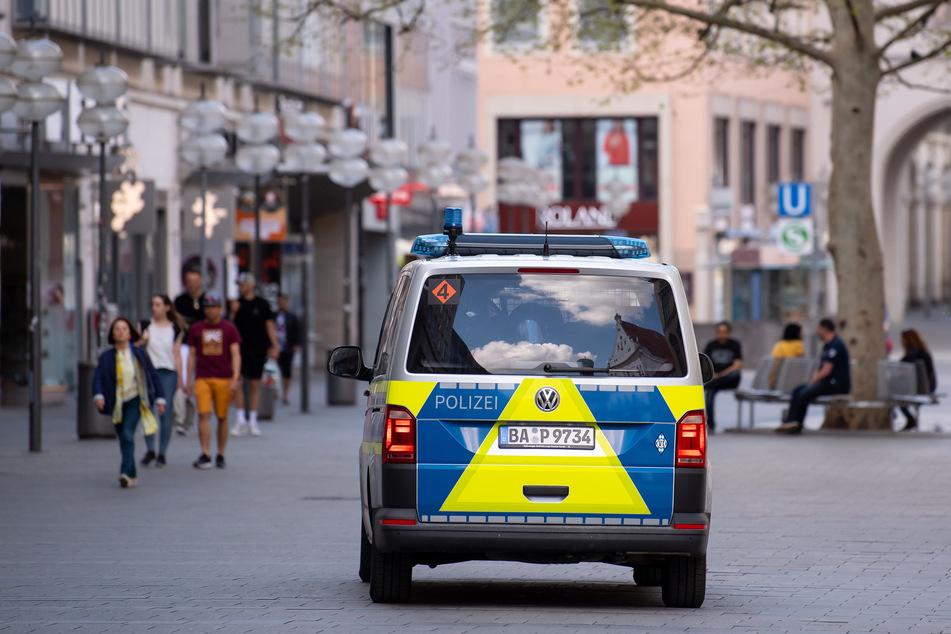 Ein Polizeiauto fährt durch eine Fußgängerzone. (Symbolbild)
