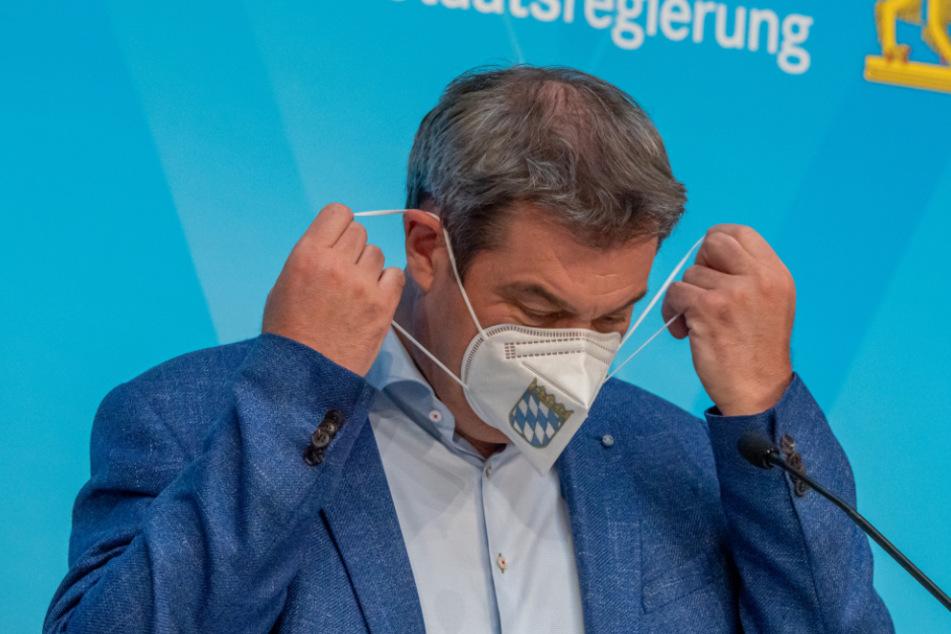 Markus Söder (CSU), Ministerpräsident von Bayern, nimmt auf einer Pressekonferenz nach der Kabinettssitzung der bayerischen Staatsregierung seine FFP-2-Maske ab.