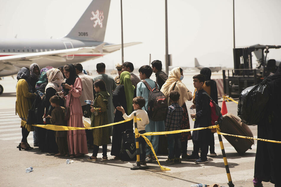 People wait to board a plane in Kabul as part of Operation Allies Refuge.