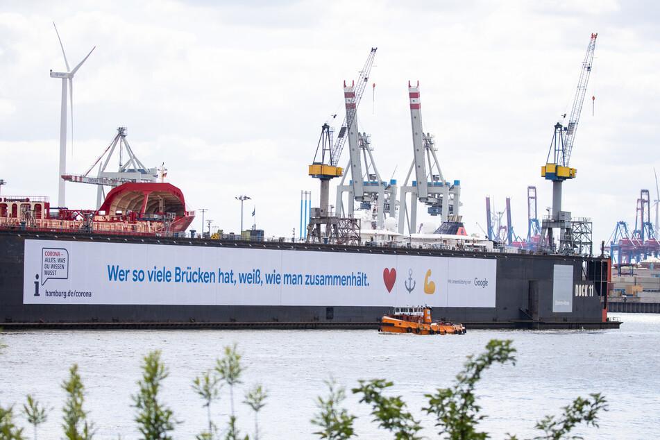 Ein großes Banner mit dem Hinweis auf ein Informationsportal zur Corona-Pandemie hängt am Schwimmdock 11 der Hamburger Werft Blohm+Voss.