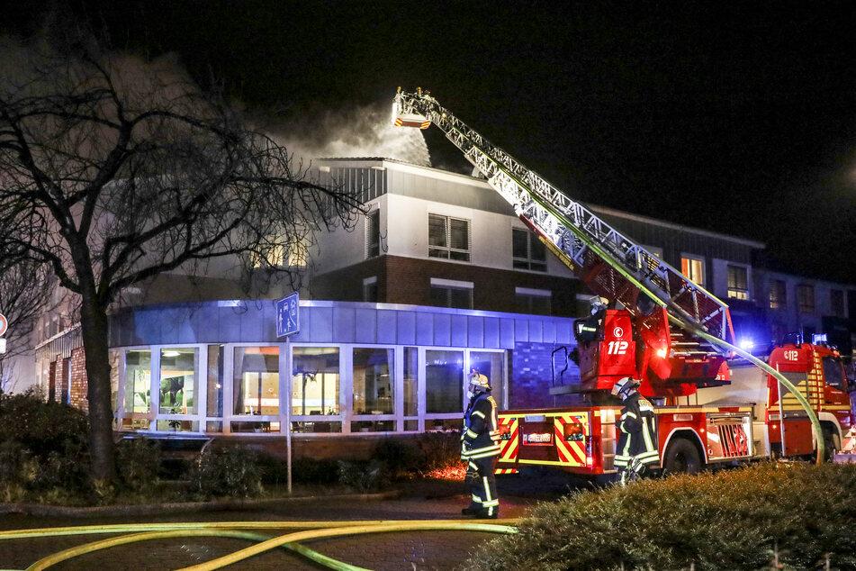 Einsatzkräfte der Feuerwehr löschen mit einer Drehleiter den Brand in dem Altenheim.