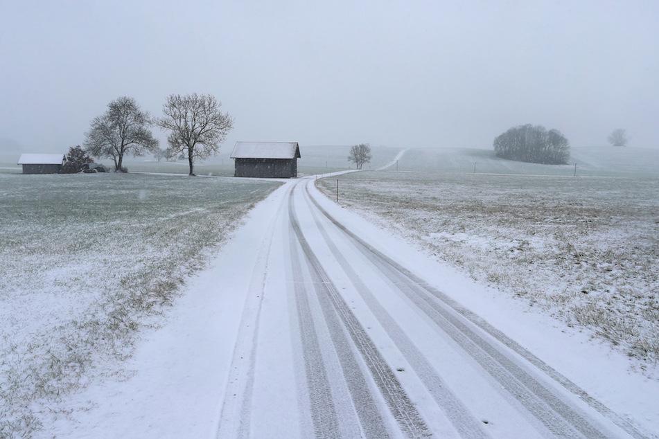 Im Schneetreiben führt eine Landstraße durch die Allgäuer Landschaft.