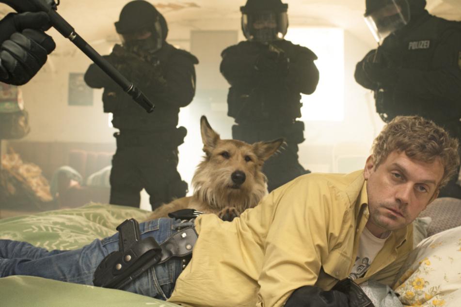 """Eine Szene aus """"Grießnockerlaffäre"""": Der verkaterte Franz Eberhofer (Sebastian Bezzel) und Hund Ludwig werden unsanft vom SEK geweckt."""