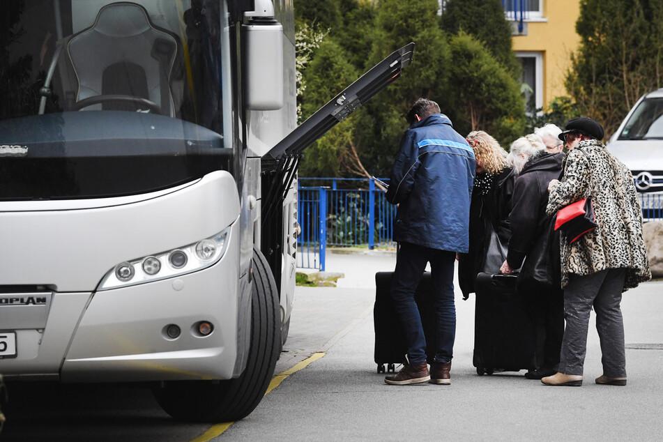 Touristen stehen an einem Reisebus.