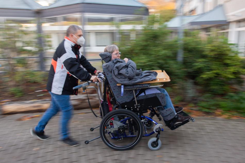 Ein Mitarbeiter der Assistenz schiebt einen Bewohner in seinem Rollstuhl über einen Hof an einer Diakonie-Wohnstätte.