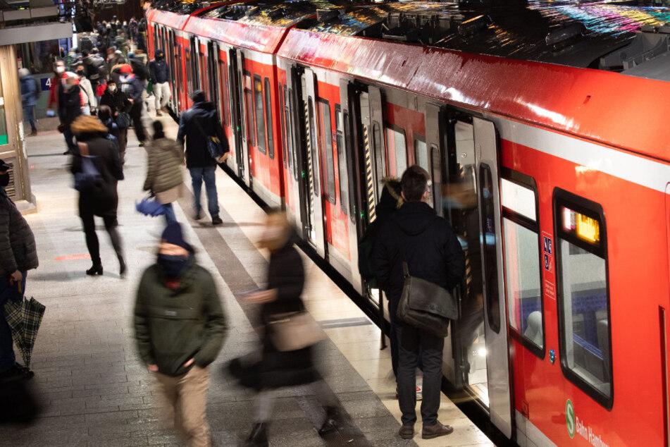 Mit Mund-Nasen-Schutz sind Fahrgäste am Hauptbahnhof auf einem S-Bahnsteig unterwegs.