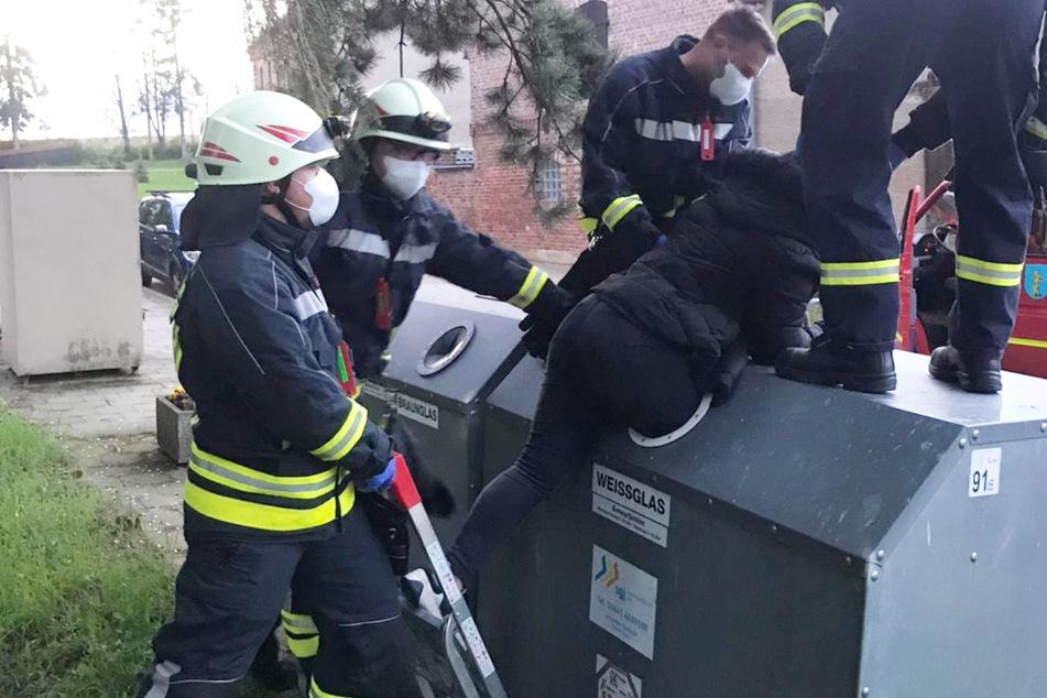 Die Feuerwehr versucht das Mädchen aus dem Container zu ziehen.