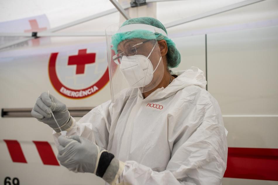 Eine Mitarbeiterin des Gesundheitspersonals bearbeitet einen Corona-Test in Lissabon. Die Stadt wurde kürzlich aufgrund der Ausbreitung der Delta-Variante für zweieinhalb Tage abgeriegelt.