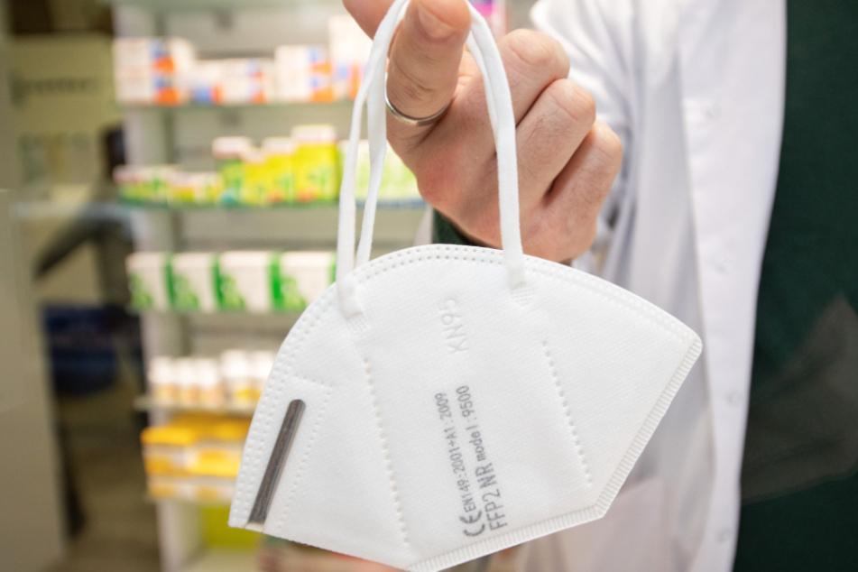 Ein Apotheker hält zur Illustration eine FFP2-Maske an einem Finger.