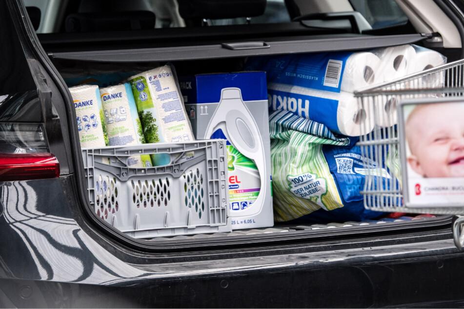 Ein mit zahlreichen Einkäufen gefüllter Kofferraum ist auf dem Parkplatz eines Supermarktes zu sehen.