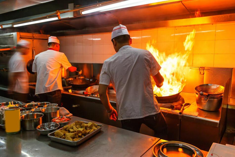 Mitarbeiter eines Restaurants stehen in einer Küche. (Symbolbild)