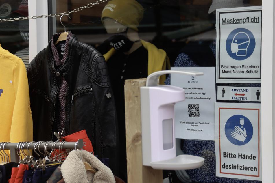 Die Schilder neben der Eingangstür eines Bekleidungsgeschäftes weisen darauf hin, dass im Laden Maskenpflicht besteht und die Hände desinfiziert werden müssen.