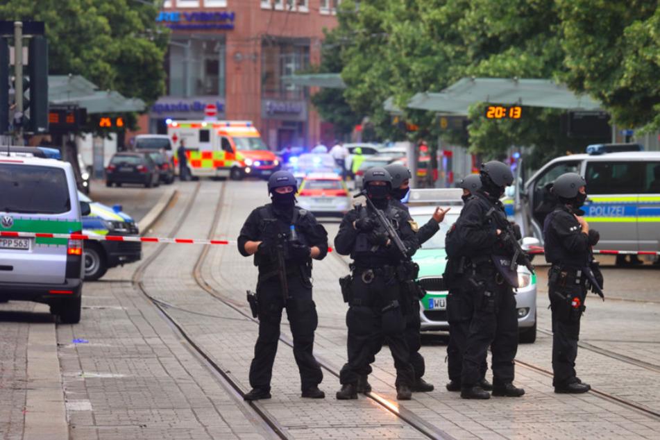 Polizisten stehen in Würzburg. Bei dem Angriff in der Innstadt wurden drei Frauen getötet und sieben Menschen verletzt.