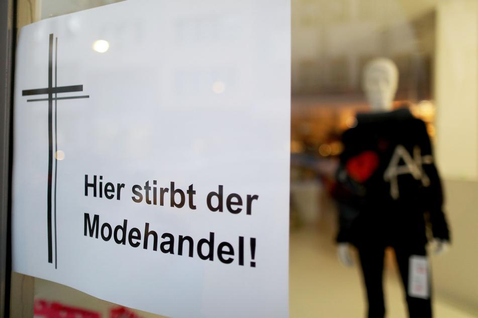 """""""Hier stirbt der Modehandel"""": Ein Geschäft in Köln weißt mit einem Plakat auf seine große Not hin."""
