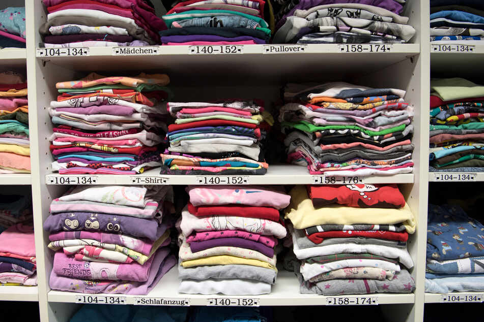 Kleidung liegt in den Regalen einer Kleiderkammer.