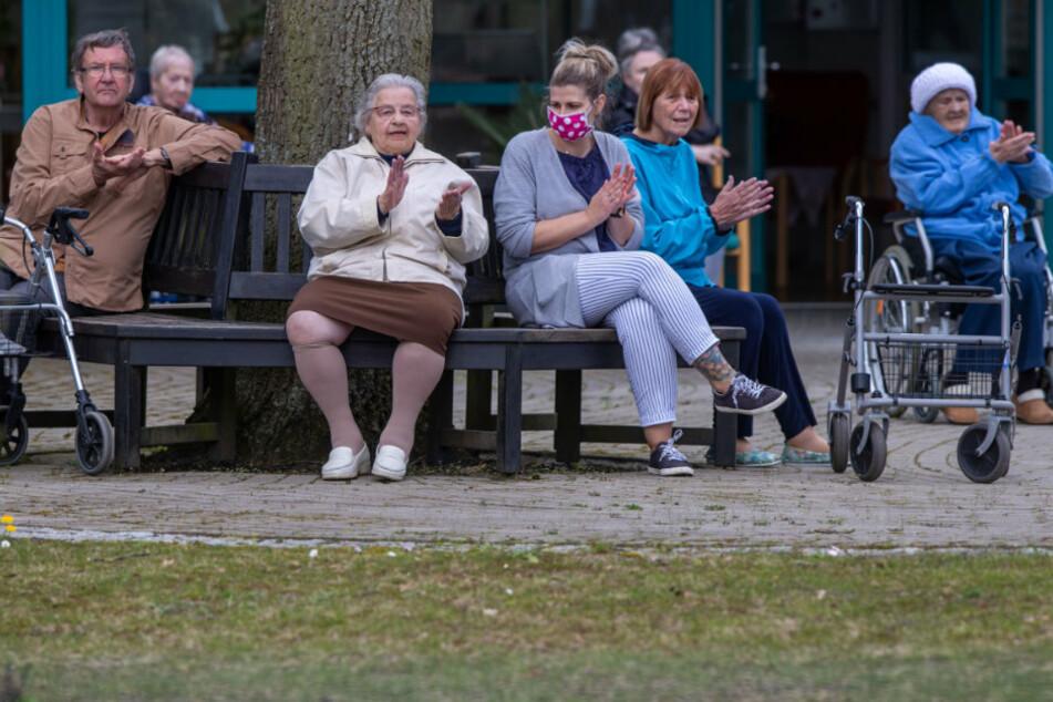 Bewohner und Pflegekräfte applaudieren nach kleinen Konzert vor dem AWO Seniorenhaus Schelfwerder, das wegen der Corona-Krise für Besucher gesperrt ist.