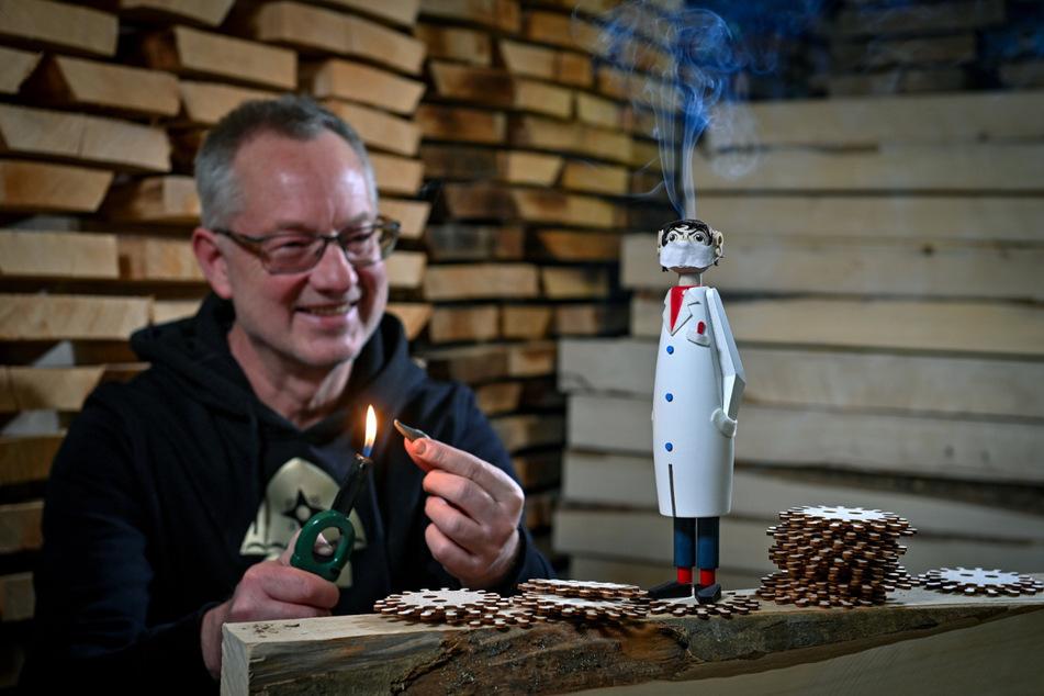 """Tino Günther ist stolz auf seinen """"Räucher-Drosten"""". Dem Räuchermann kommt wegen des Mund-Nase-Schutzes nicht wie sonst üblich der Rauch aus dem Mund - ihm raucht vielmehr der Kopf."""