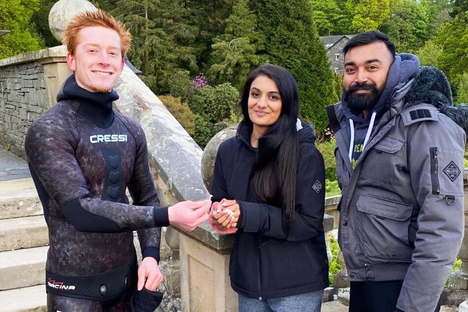 Taucher Agnus Hosking (l.) gibt einem Paar ihren Verlobungsring wieder. Der Ring war Rebecca Chaukira vom Finger gerutscht, als ihr Freund Viki Patel den Antrag machte.