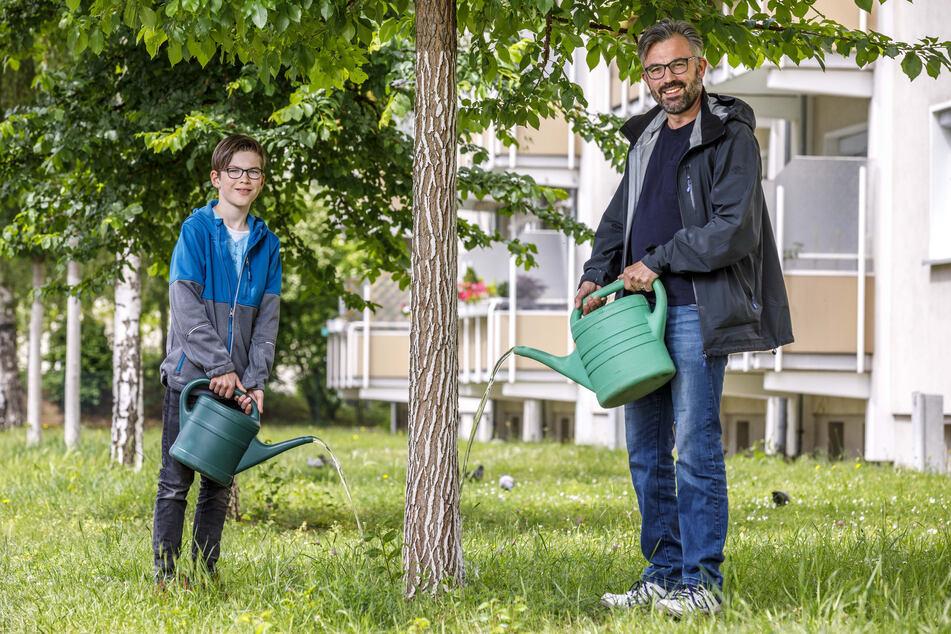 """Ronny Scholz (43) von """"Mein Baum, mein Dresden"""" und sein Sohn Dylan (10) legen schon mal vor und gießen einen Baum vor ihrer Haustür. Das Berliner Modell hätten sie gern auch für Dresden."""