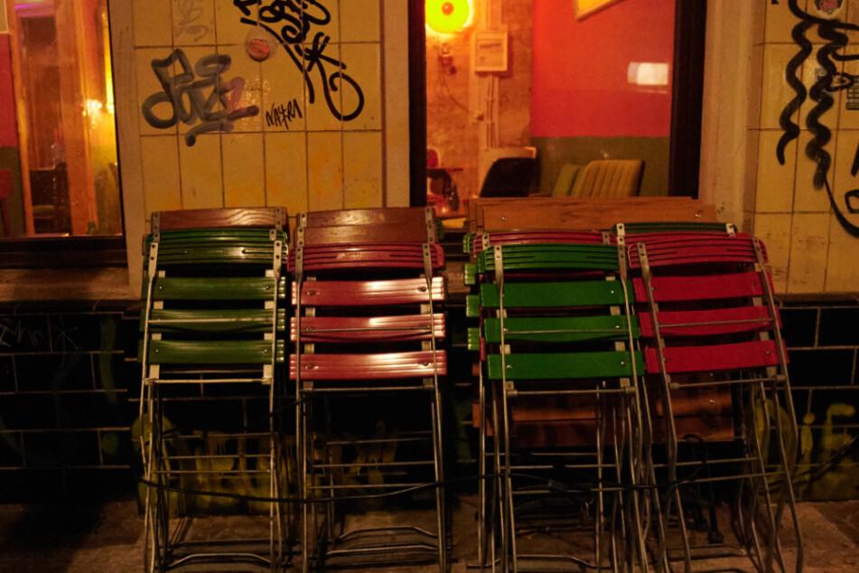 Kurz nach der Sperrstunde stehen zusammengeklappte Stühle vor einer Bar in Neukölln.