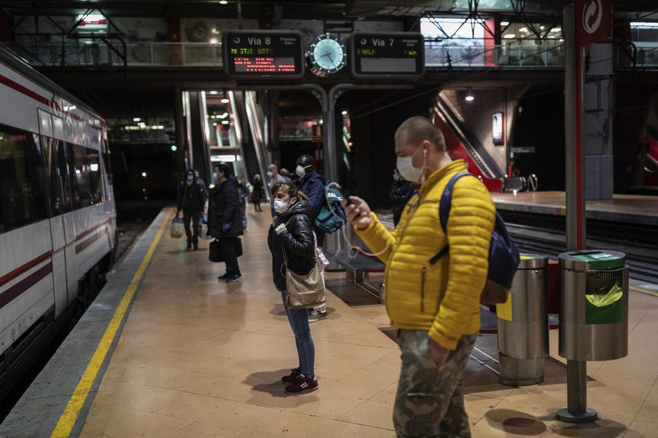 Pendler tragen Gesichtsmasken zum Schutz vor Coronaviren auf einem Bahnsteig des Bahnhofs Atocha in Madrid.