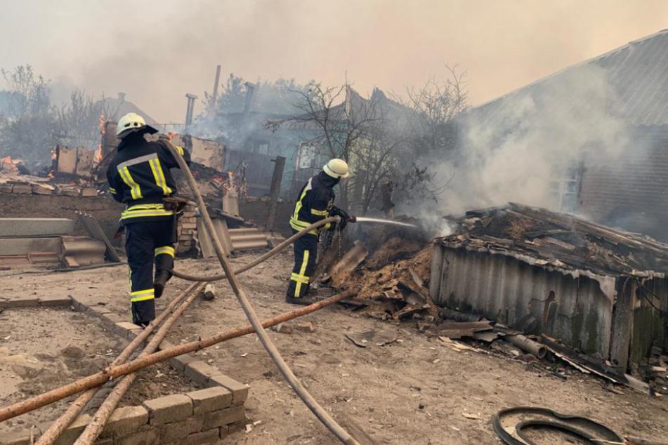 Einsatzkräfte der Feuerwehr löschen den Brand in der Kleingartensiedlung.