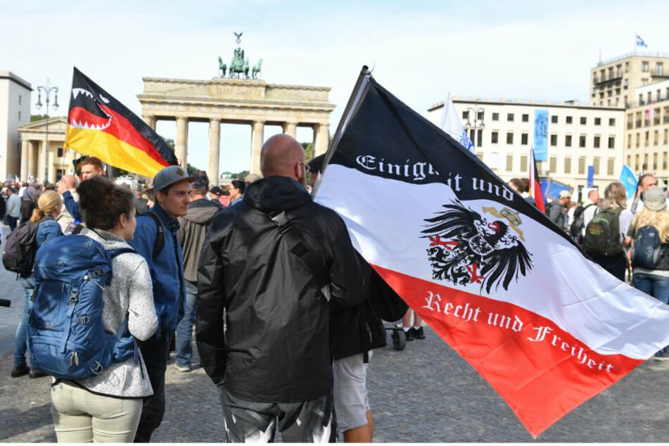 Ein Teilnehmer hält vor einer Demonstration gegen die Corona-Maßnahmen eine Reichsflagge vor dem Brandenburger Tor.
