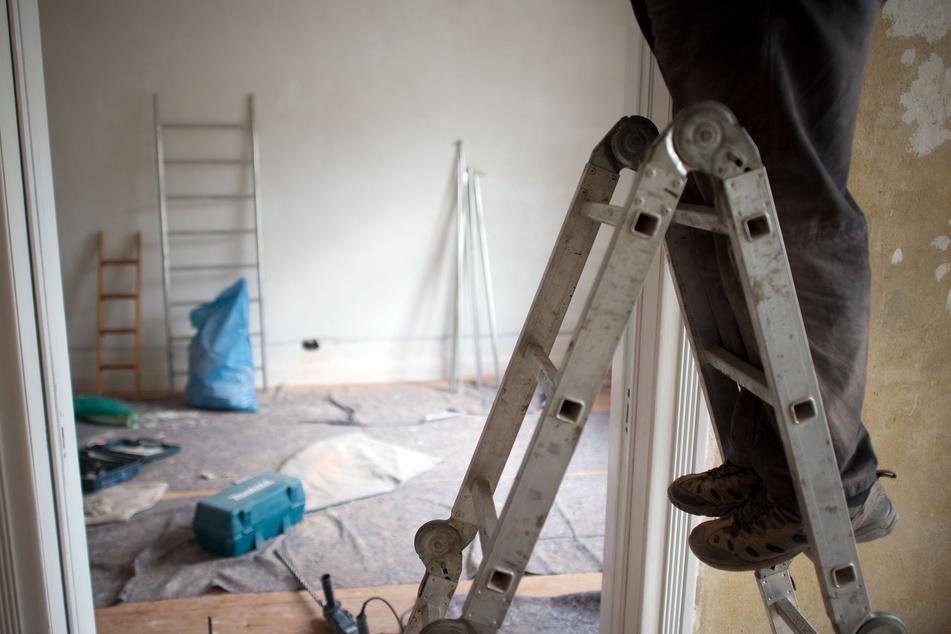 Ein Handwerker arbeitet in einer Wohnung.