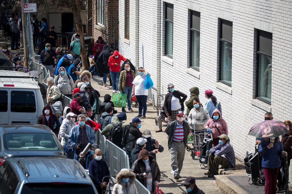 Menschen stehen Schlange vor einer Lebensmittelausgabe für Bedürftige im New Yorker Stadtteil Brooklyn. Seit Mitte März haben in den USA bereits Millionen Menschen mindestens zeitweise ihren Job verloren - so viele wie nie zuvor in solch kurzer Zeit.